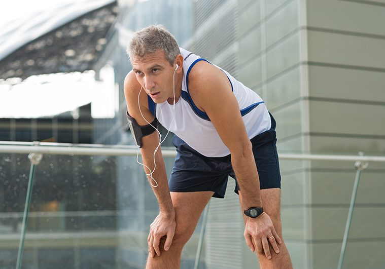 Portrait Of Exhausted Male Jogger Resting In A Urban Place